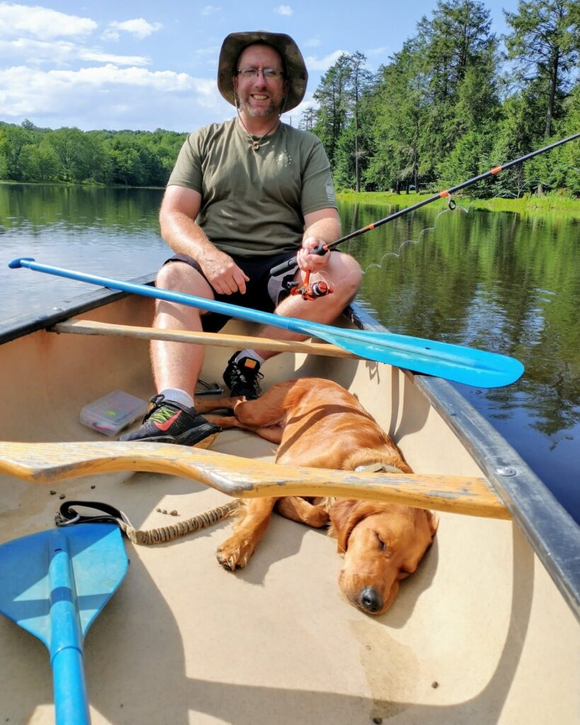 stand with me handler and dog in rowboat on lake